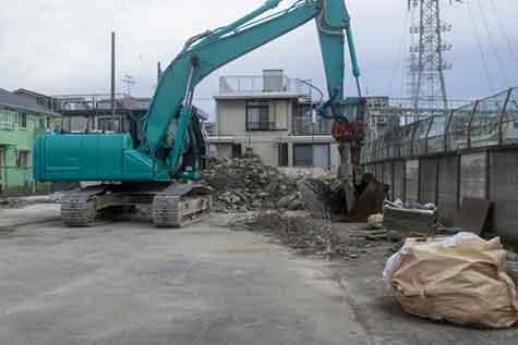 コンクリートを砕くユンボ